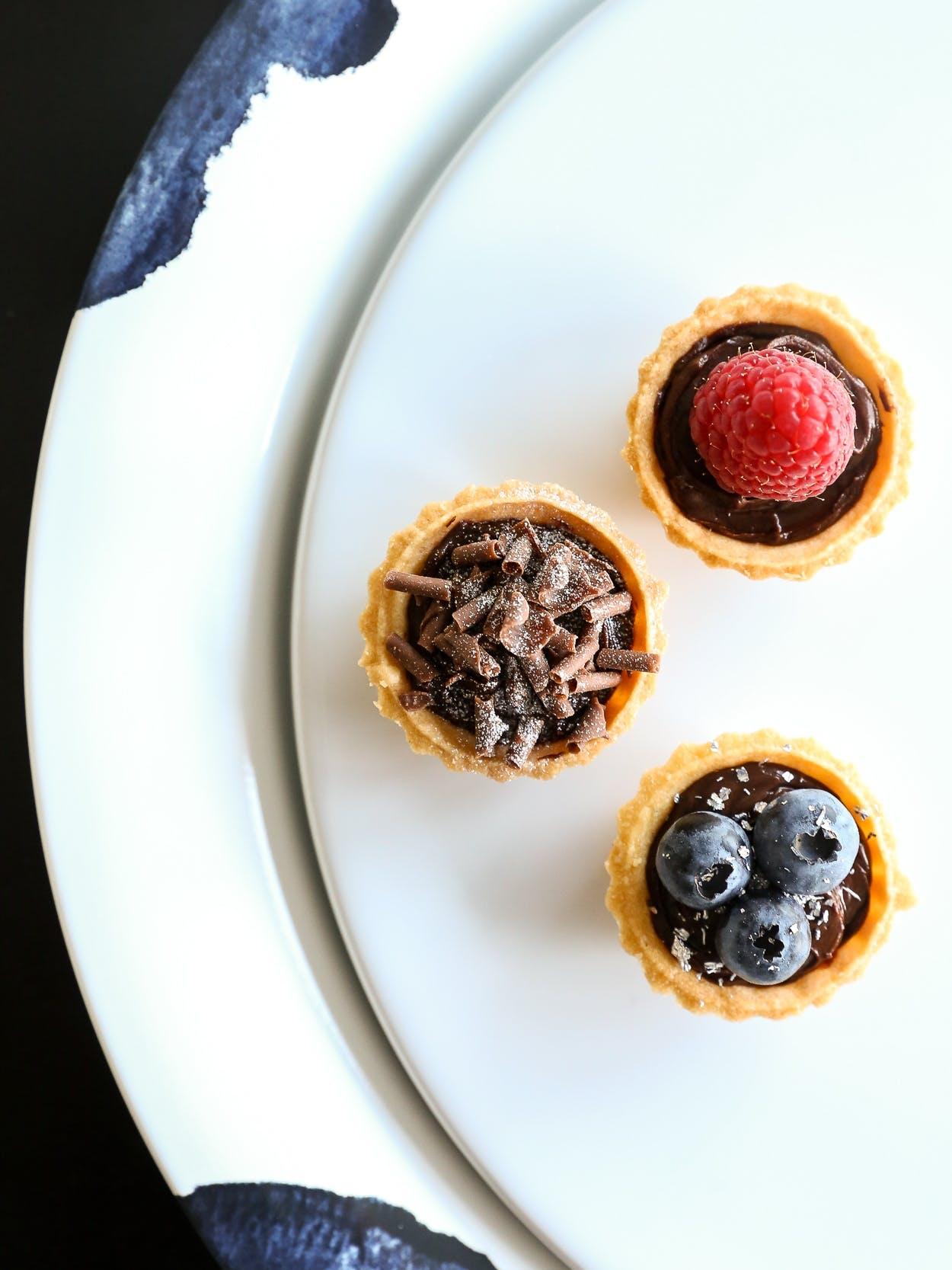 Her er et eksempel på de perfekte hapsere til sommerfesten - færdigkøbte tærteskaller med chokoladeganache, bær og pynt.