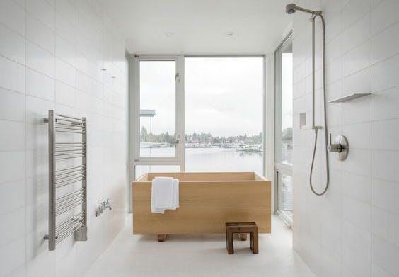 hvidt badeværelse med store panoramavinduer og badekar i træ