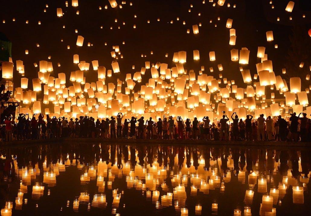 Lanterne festival i Thailand med lanterne der spejler sig i en sø