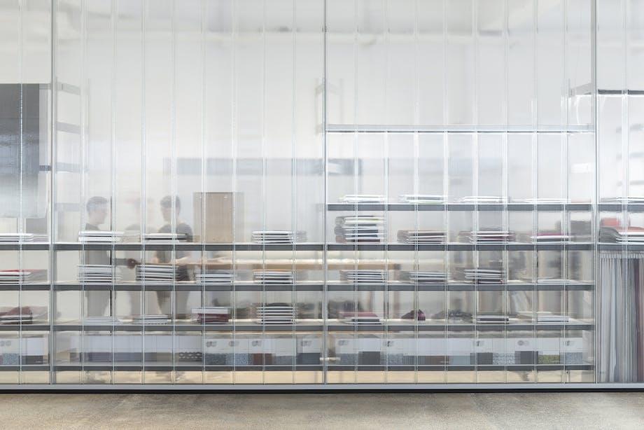 Rummet er på begge sider kantet af store glasvægge. Her med kig til Kvadrats bibliotek, som de kalder samlingen af prøver fra hele deres kollektion.