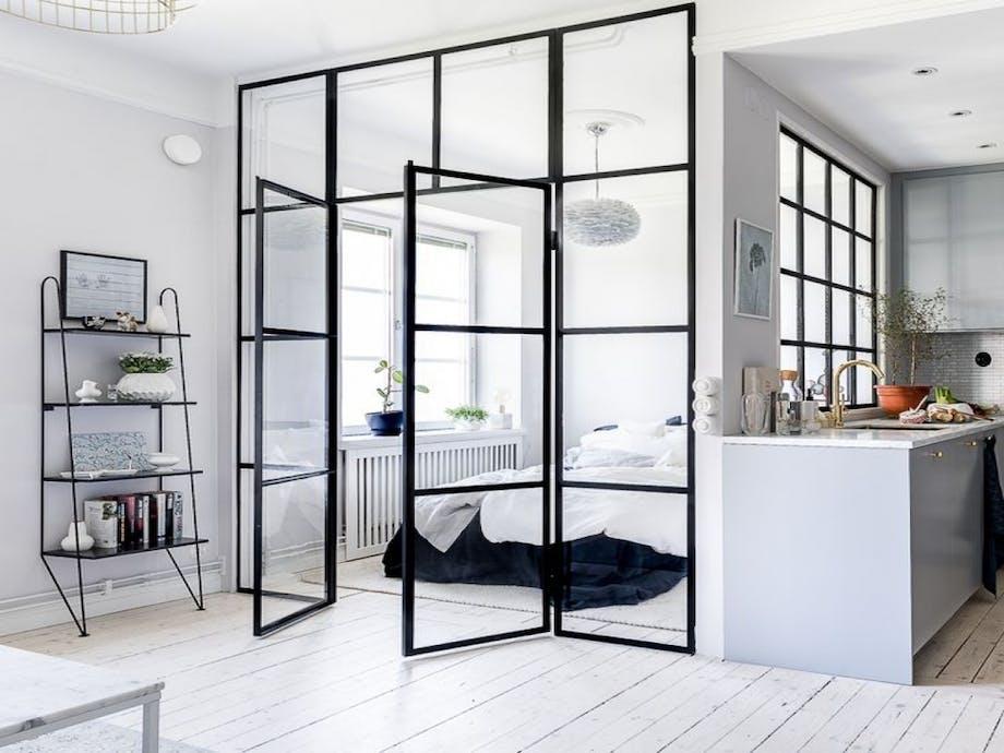 rumdeler i glas og jern separerer stue og soveværelse