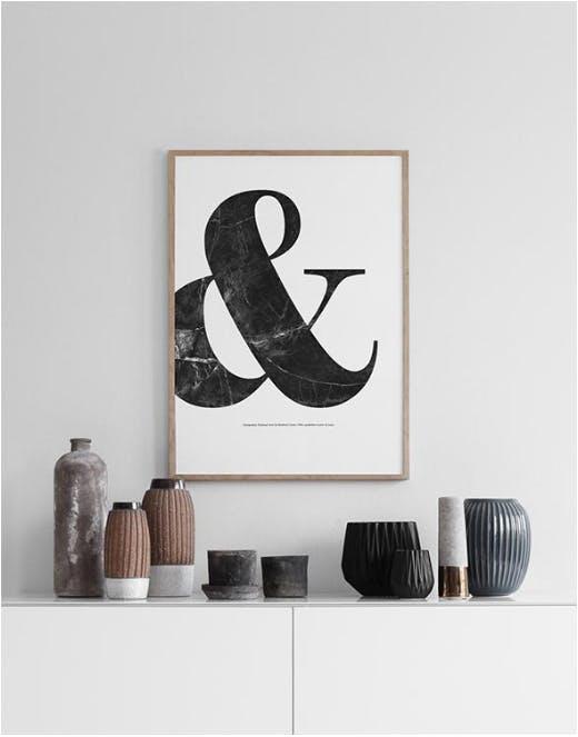 Desenio plakat af citat hængende over et bord