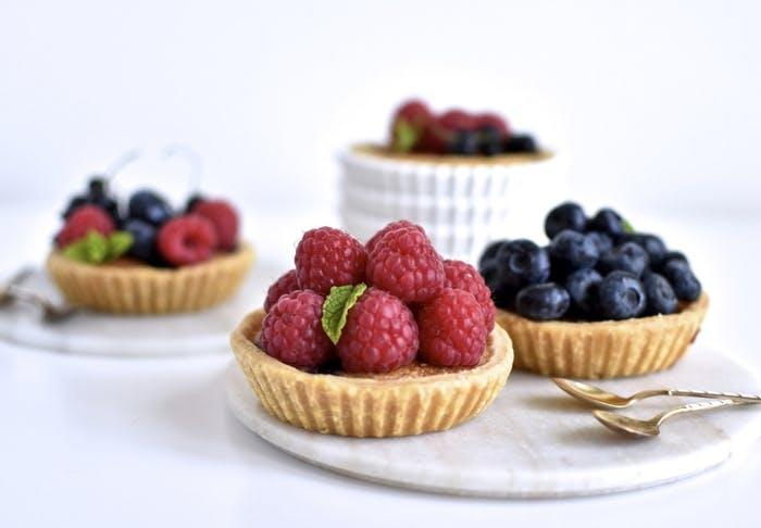 Små tærter med friske hindbær og blåbær.