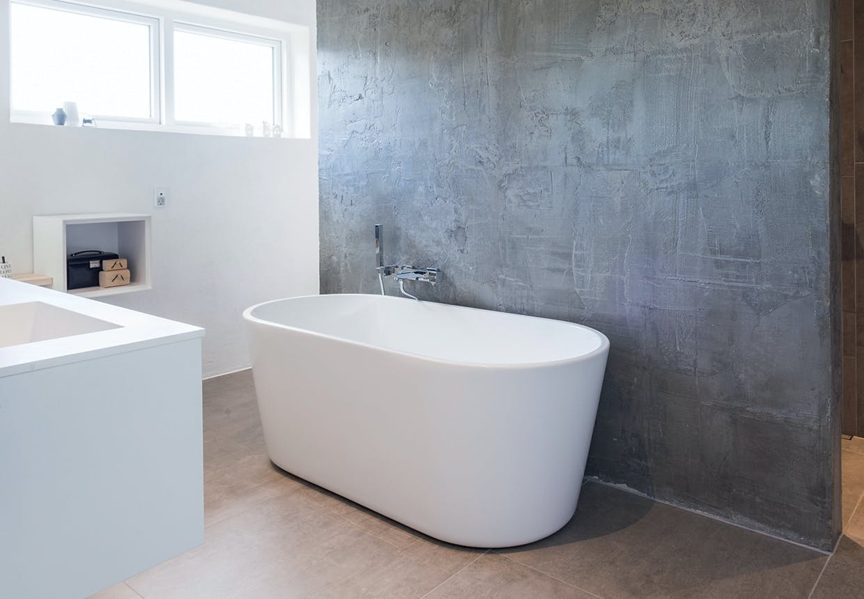 Badekar med betonmur som baggrund