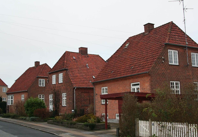 Tre ikoniske røde murermestervillaer på rad og række.
