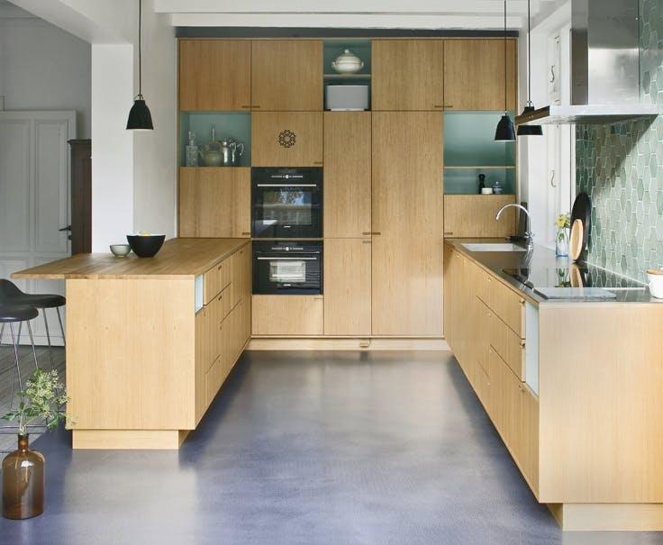 Tonede gulve og farver på væggen står i flot konstrast til dette håndlavede køkken fra Nicolaj Bo.