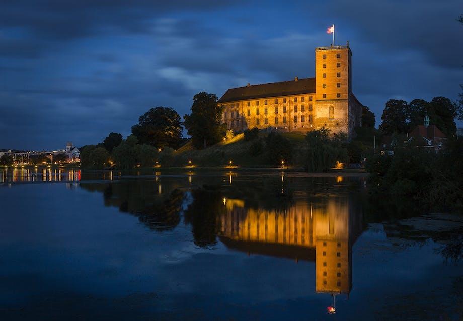 Koldinghus spejler sig i Slotssøen i tusmørket