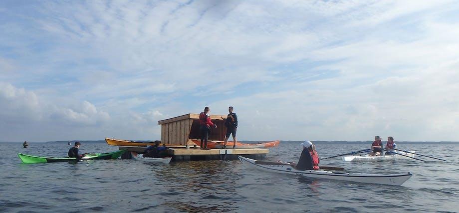 Kajakroere mødes på vandet ved havshelter i Roskilde fjord i Halsnæs Kommune