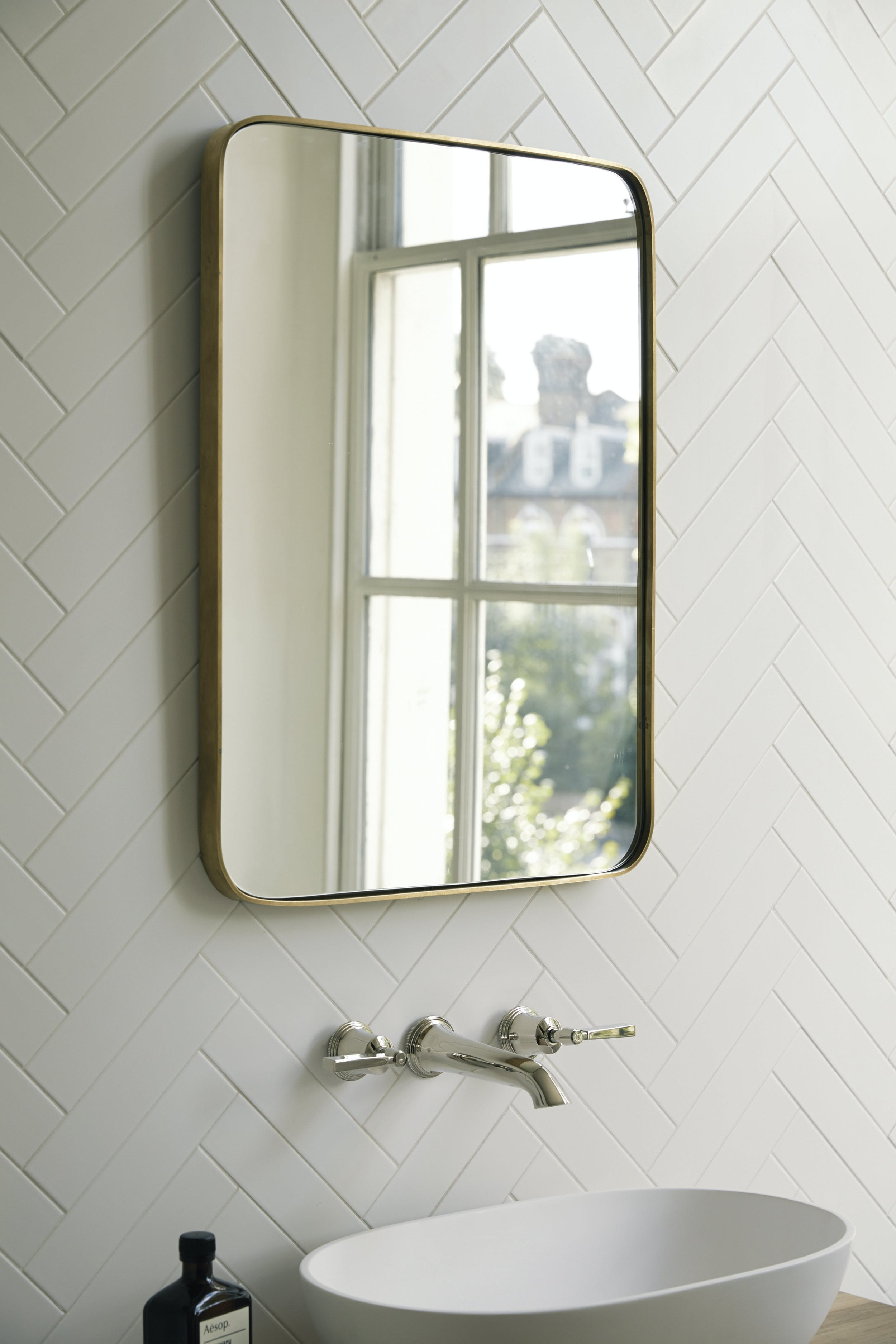 rundt spejl i messing badeværelse