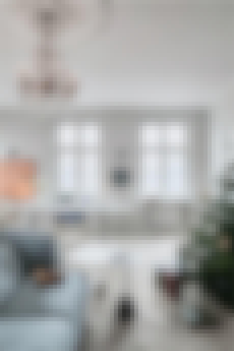stue med stor lysekrone og grå sofa og juletræ