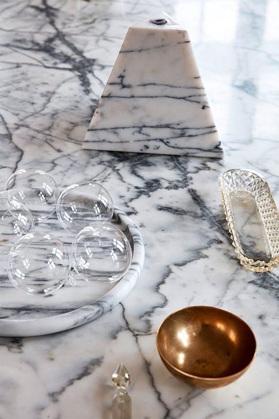 marmor bord med lille bronze skål og lysestage i marmor