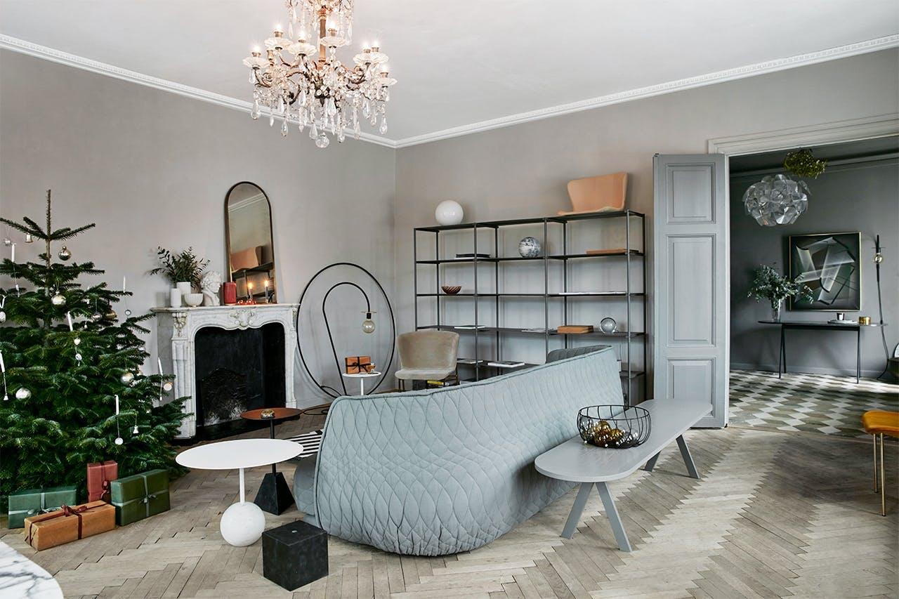 stue med stor lysekrone og juletræ og sofa og pejs