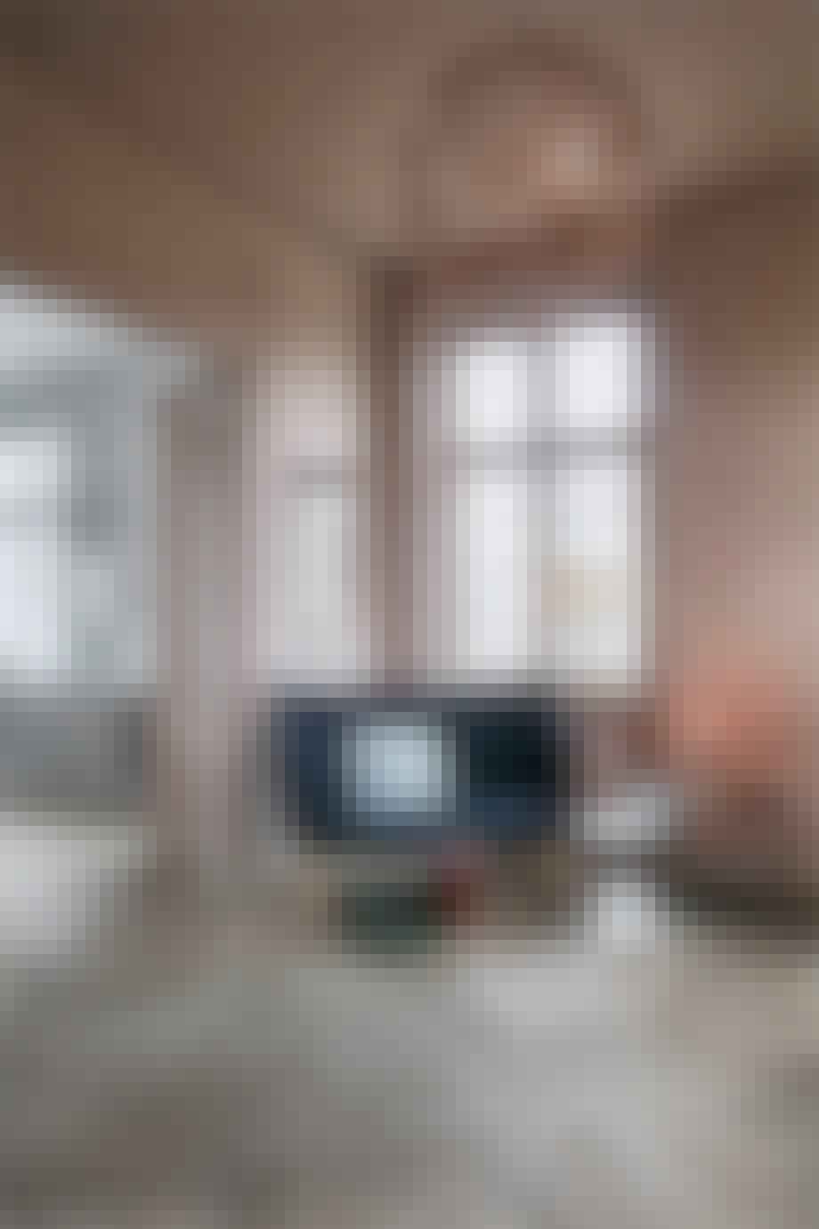 stue med rosa vægge og stor loftlampe og en mørkeblå sofa