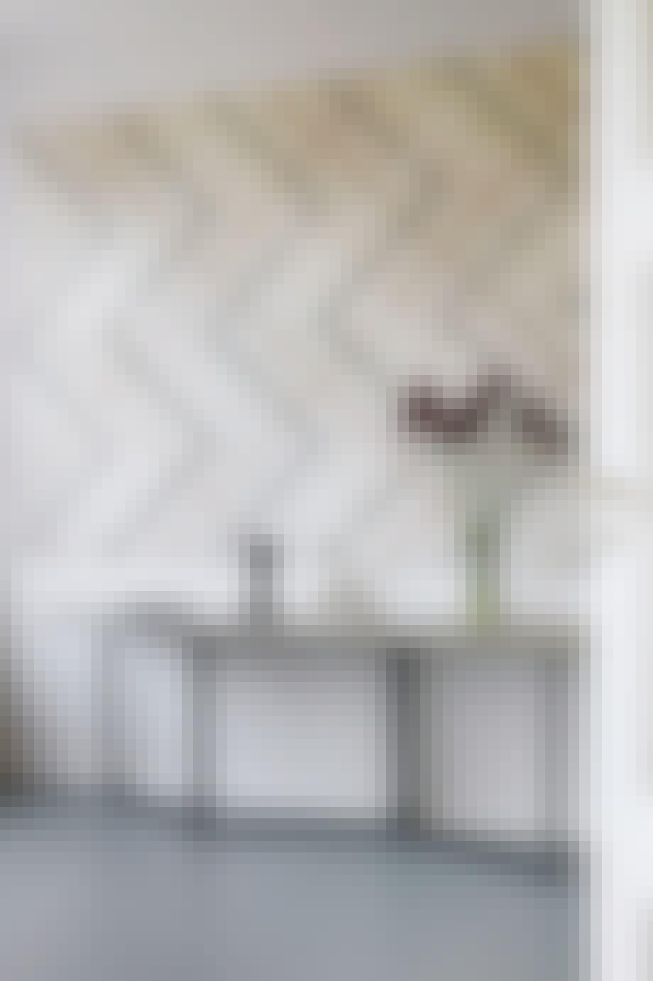 stue med stort maleri og aflangt bord og en vase med røde blomster