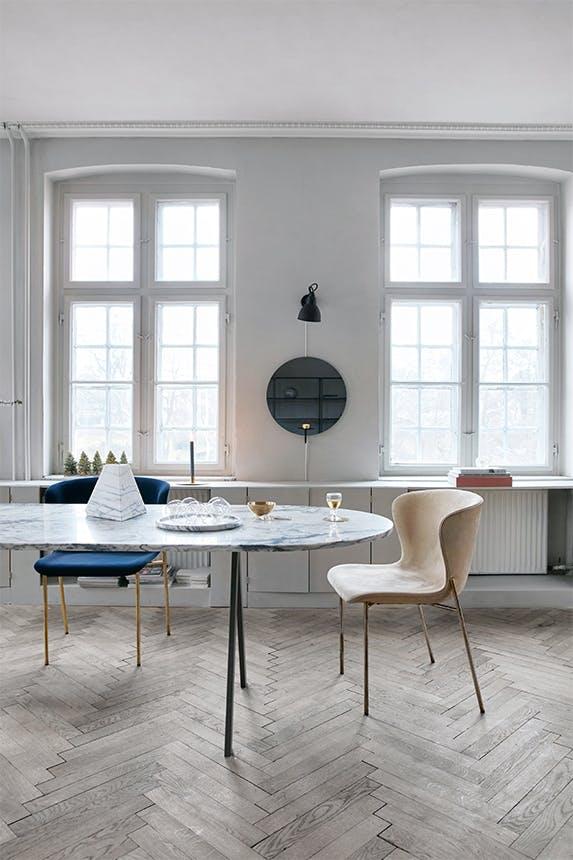 spisebord i marmor i en spisestue med sildebensparketgulv