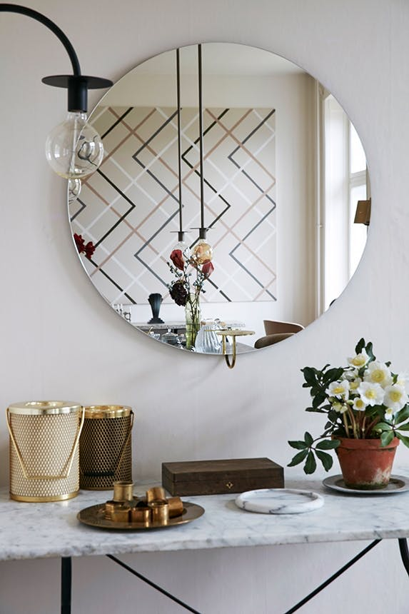 marmorbord med en potte med blomster og et stort rundt spejl over