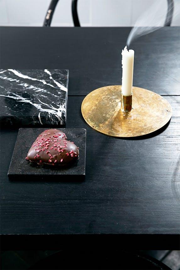 sort bord med messing lysestage og en tallerken med et julehjerte