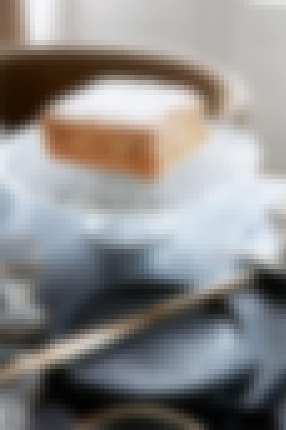kage på et glasfad med fod og messing bestik på et sort bord