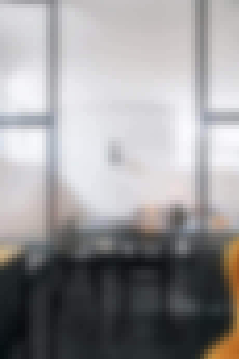 sort spisebord og stole samt en rumdeler i glas og jern
