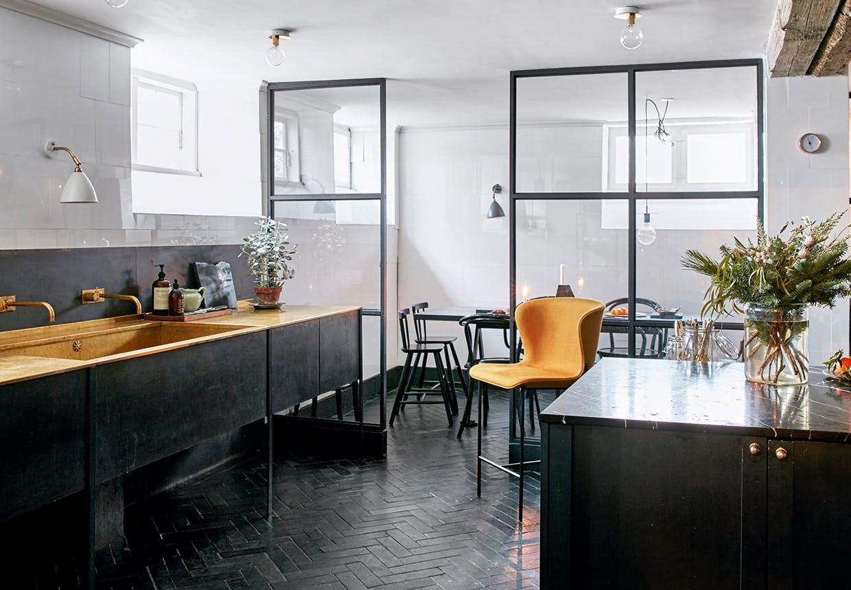 køkken i sort og orange med rumdelere i glas og jern