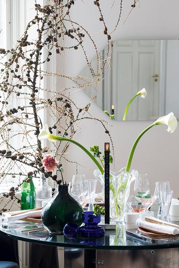 julebord pyntet med blomster, vaser og en stor troldegren