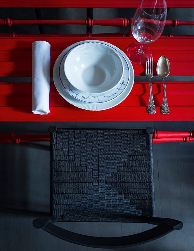 rødt julebord med hvid service og sort stol
