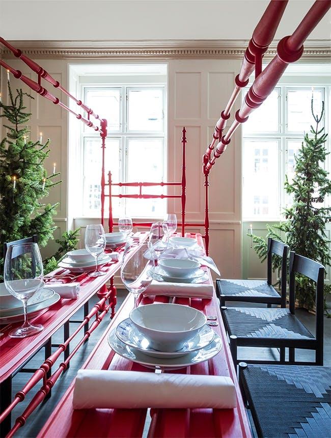 rødt og hvidt julebord og to juletræer i spisestue