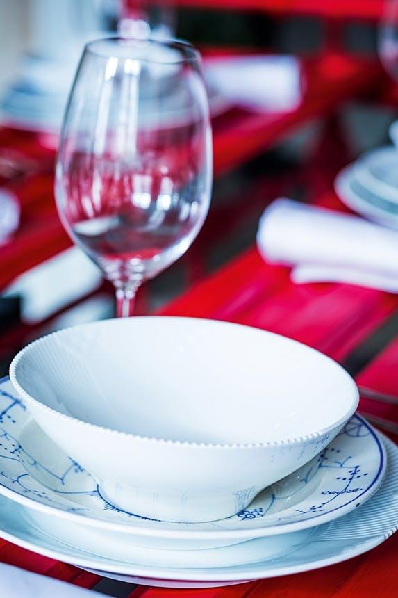 nærbillede af julebord med hvid service på rødt bord