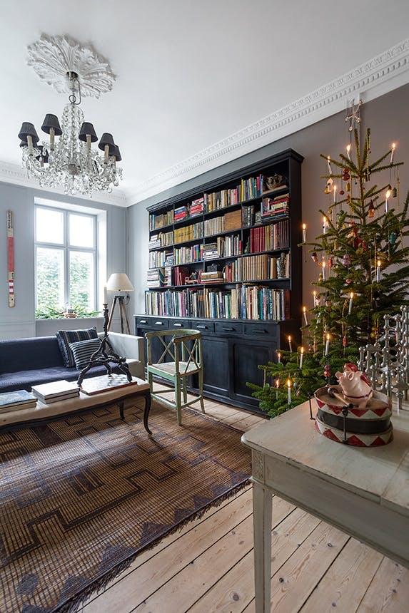 stue med juletræ og stor bogreol og sofa