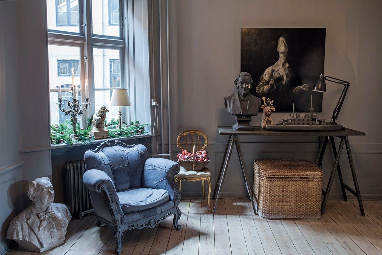 blå stol i stue og et bord og et maleri og en statue