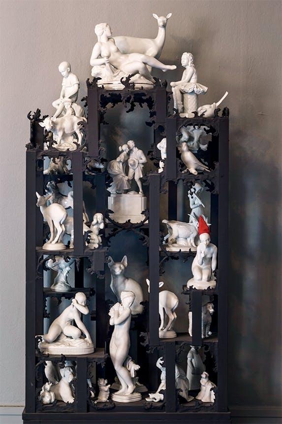 42 porcelænsfigurer fra serien royal whites udstillet i sort skab