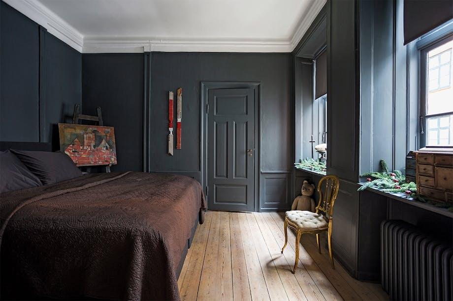 soveværelse i mørke farver og en guld stol