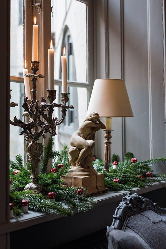 vindueskarm med gran og stor lysestage og lampe og en figur