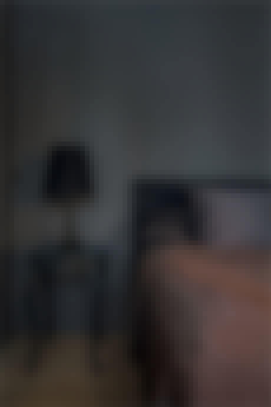 soveværelse i mørke farver og sengebord i sort med sort lampe på