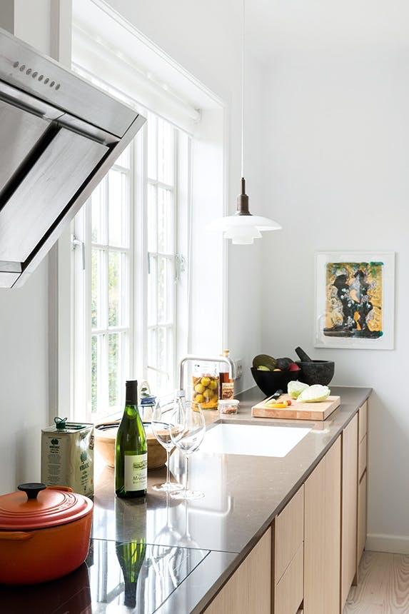køkken i lyst træ og stenbordplade
