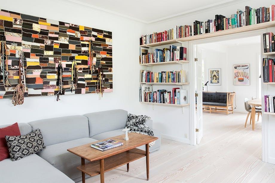 stue med sofahjørne og bøger på bogreolvæg