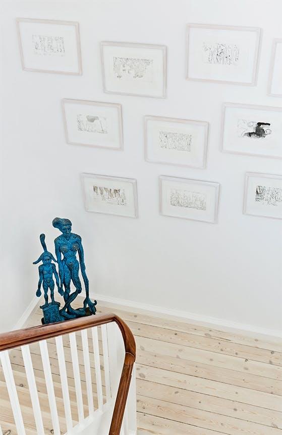 trappeopgang med blå skulptur og billedvæg