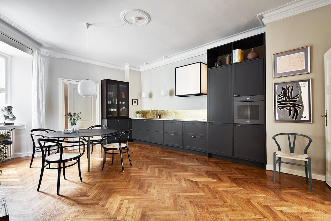 sort køkken i en lejlighed med spisebord og stole