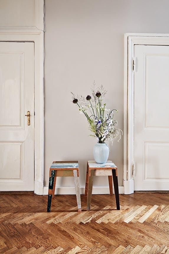 vase med blomster på et lille bord i en gang