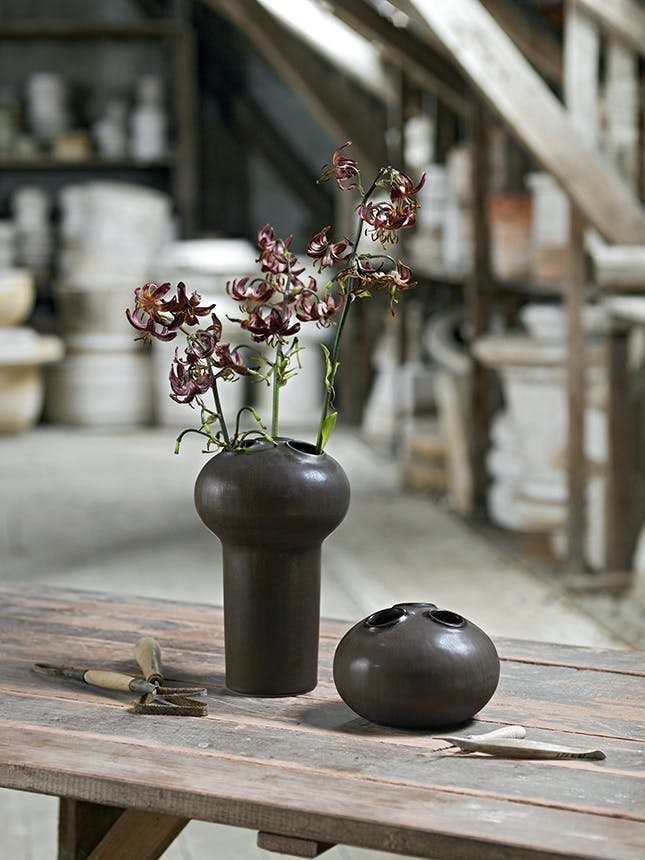 to brune krukker på bord med blomster i