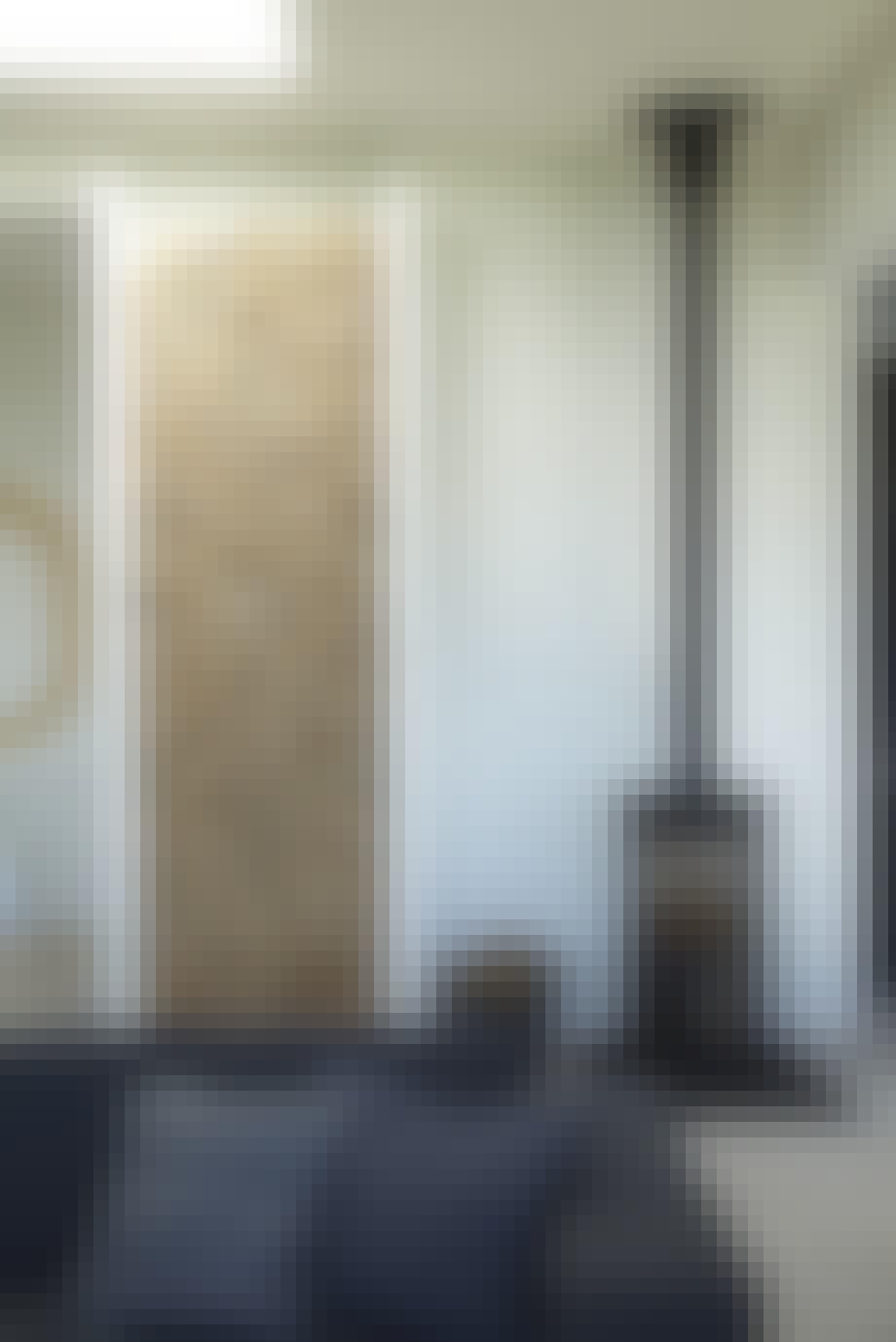 væg med brænde fra gulv til loft og en brændeovn i en stue