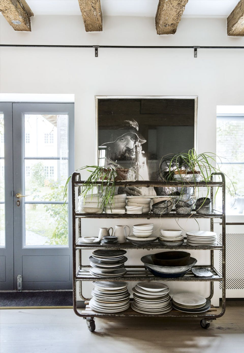 køkken med stort fotografi på væggen og en gammel rullevogn