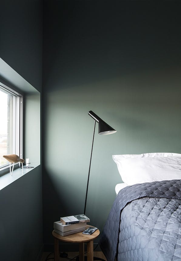 soveværelse med seng og grøn væg