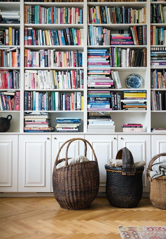 Stor bogreol fyldt med bøger og flettede kurve