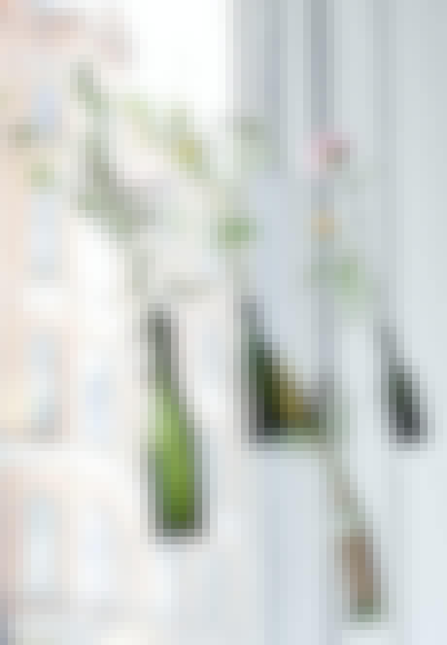 Grønne patentflasker svævende ved vindue med enkelte blomster i