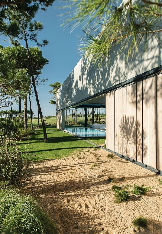 Have med træer, græsplæne, sand og adgang til swimmingpool