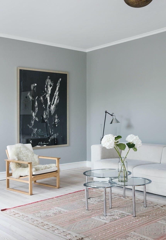 Sofastue med stor hvid sofa, enkel indretning og grå vægge