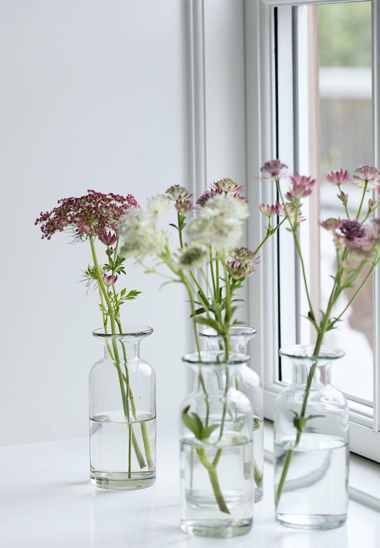 Fine glasvaser med enkelte vilde blomster