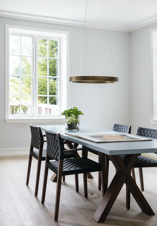 Spisestue med markant spisebord i røget eg med smuk lampe hængende over
