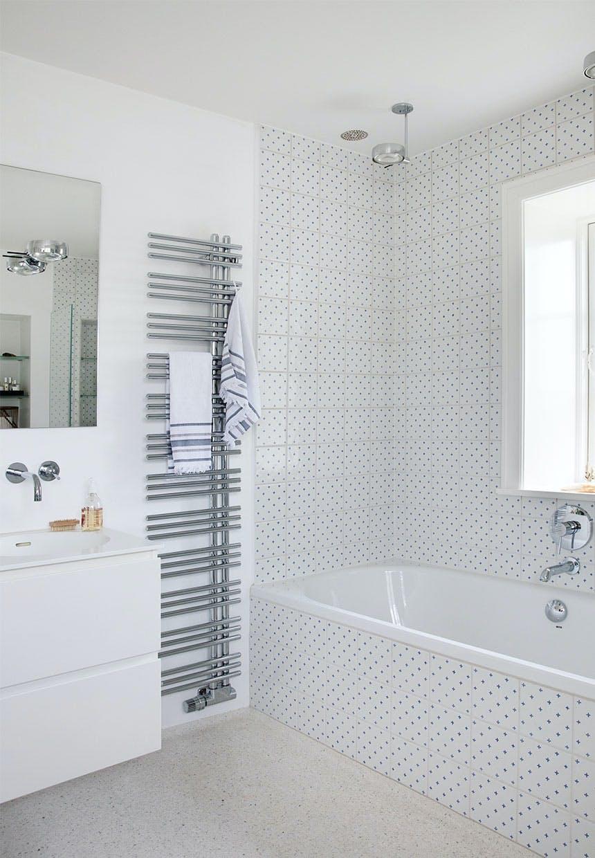 Lyst badeværelse med badekar og fliser med små blå krydser